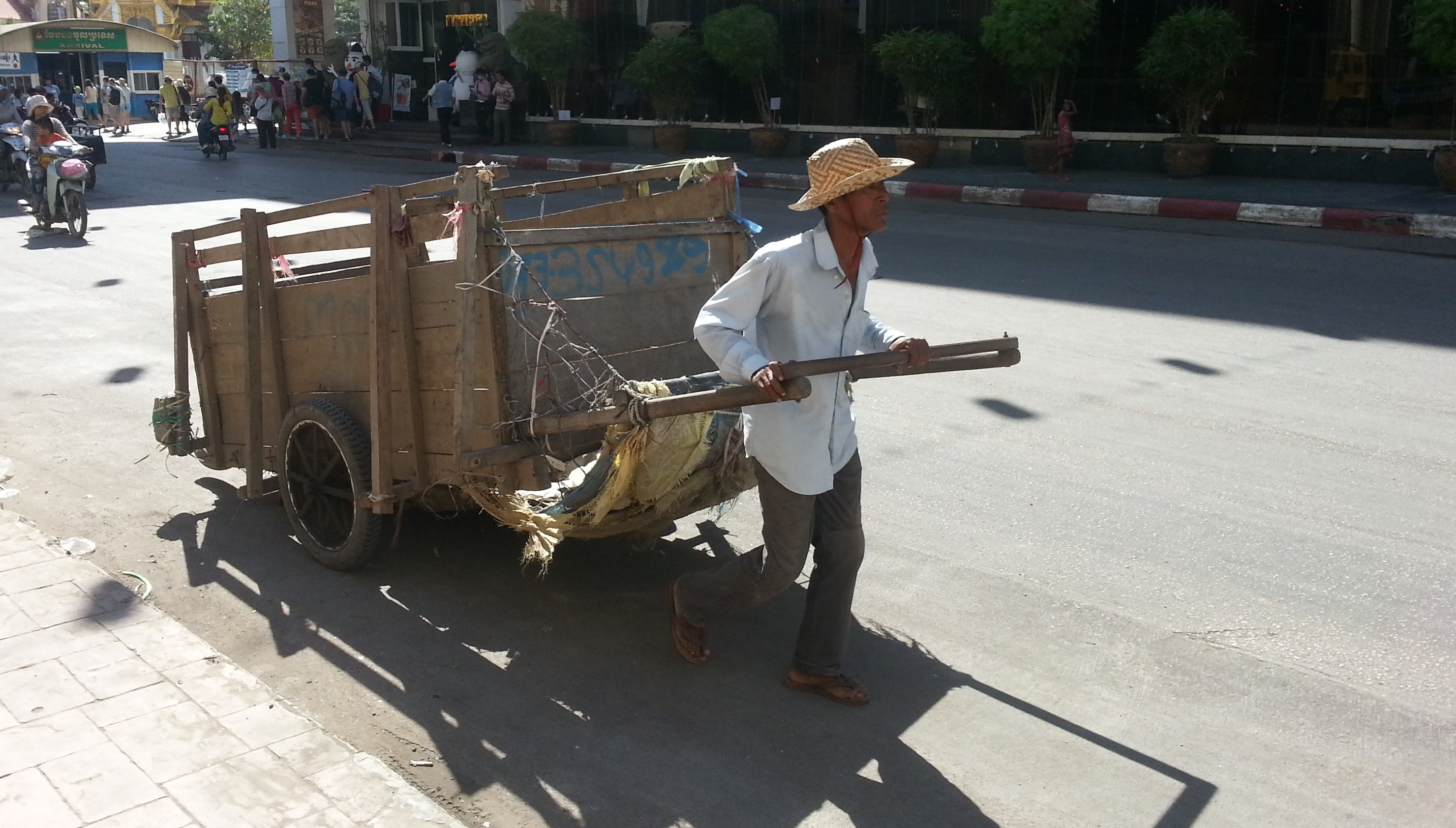 Cambodia man pulling rubbish cart on hot street